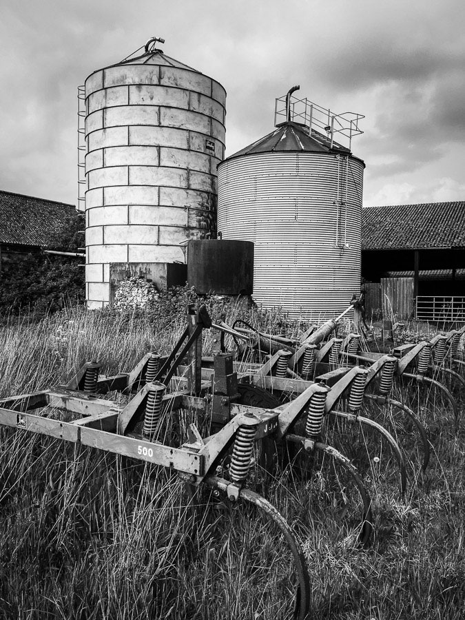 Black and white landscape photo of farm silos in Norfolk, England