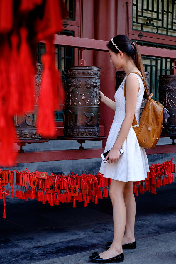 Chinese woman spinning prayer wheel in Prince Gong's mansion, Beijing, China
