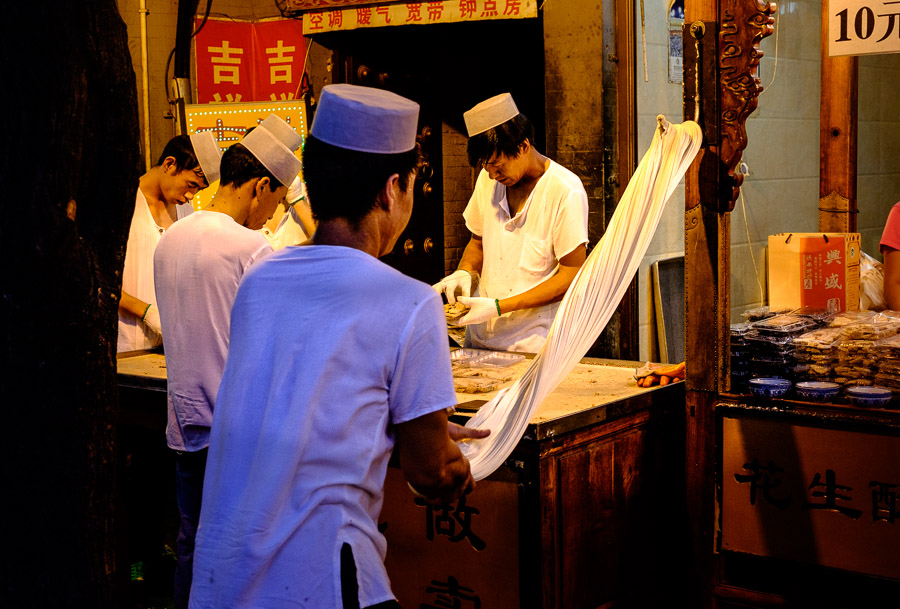 Chinese man making noodles in Muslim Quarter of Xi'an, China, at night