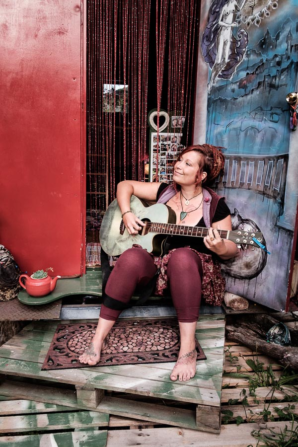 Portrait of a woman playing a guitar in front of a gypsy caravan, , illustrating an article about framing, placement and compostion.