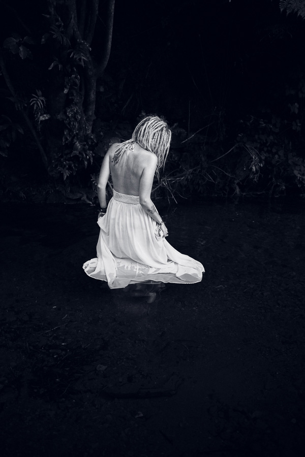 Black and white portrait of a woman with dreadlocks in water taken with a Canon 24mm lens