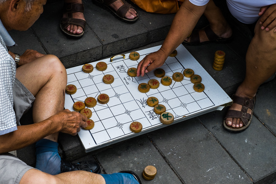 Color street photo of men playing xiangqi near the Temple of Heaven in Beijing, China