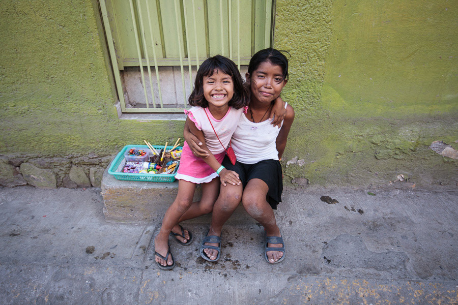 Two Mexican children selling goods in the street in Huatulco, Mexico photographed with a wide-angle lens