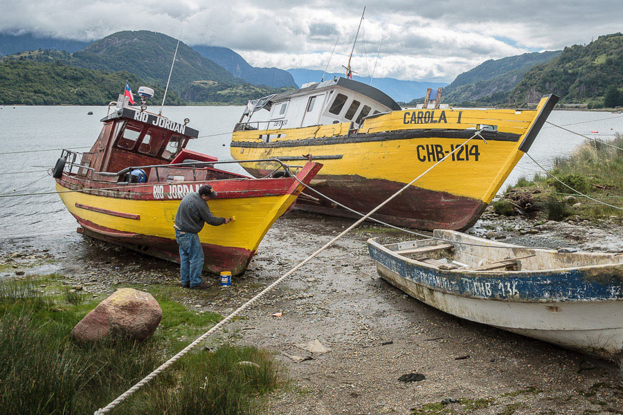 A man painting a fishing boat in Puerto Aysen, Chile photographed with a wide-angle lens