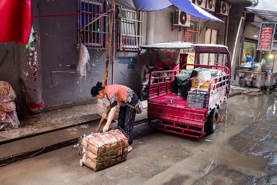 A woman sweeping up rubbish in the street in the Muslim Quarter, Xi'an, China photographed with a wide-angle lens