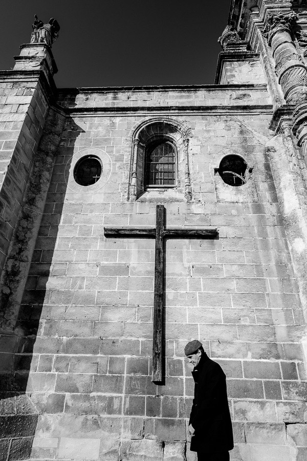 A man walking in front of a church in El Puerto de Santa Maria, Spain photographed with a wide-angle lens