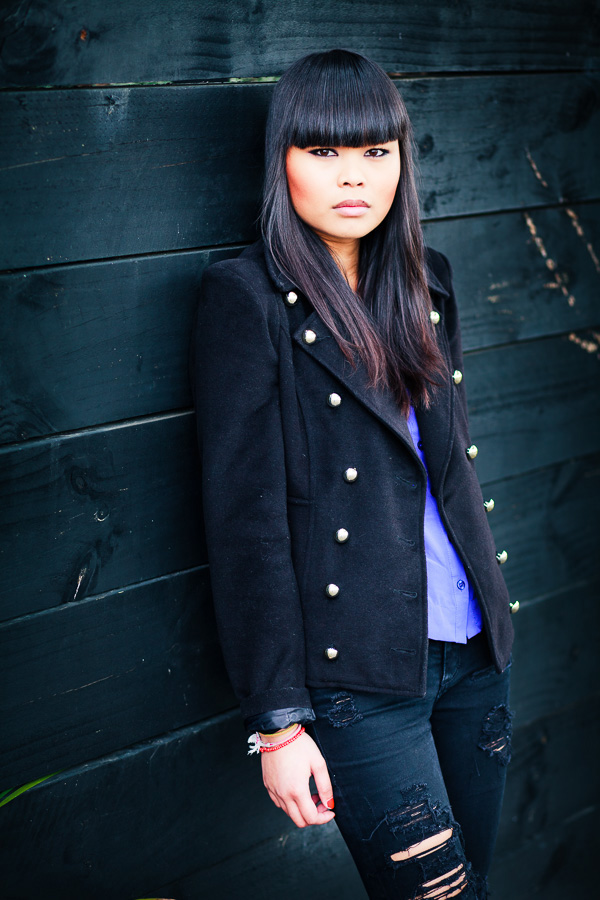 Portrait of Asian woman leaning against black fence
