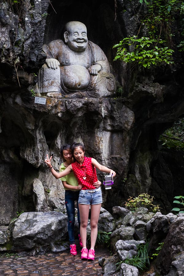 Two Chinese girls taking a selfie in front of a Buddha statue in Hangzhou, China