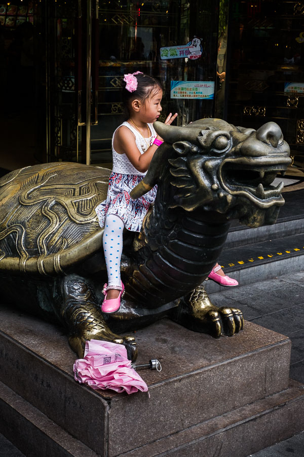 Street photo of young girl posing for a photo in Shanghai, China