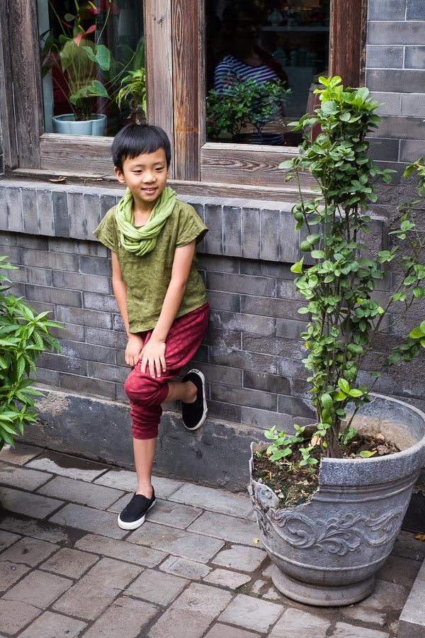 Street photo of a boy posing for a photo in a hutong in Beijing, China