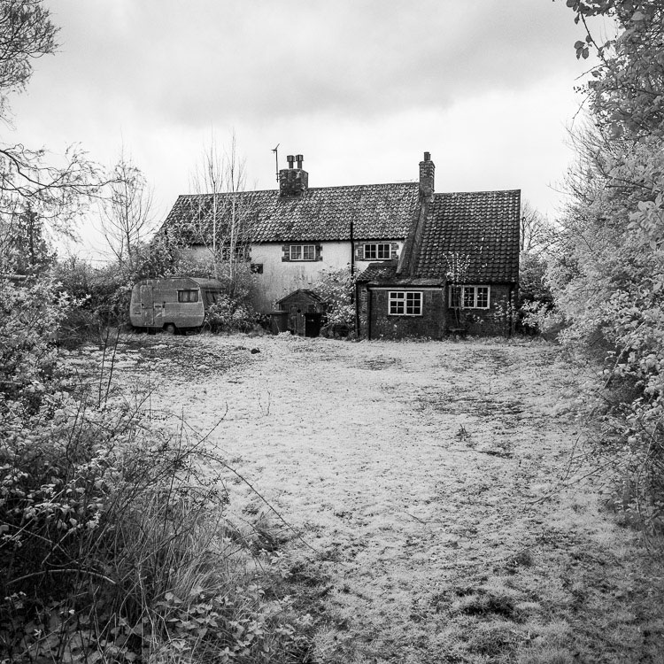 Black and white photo of an old house taken with a Fujifilm X-Pro 1 camera converted to infrared