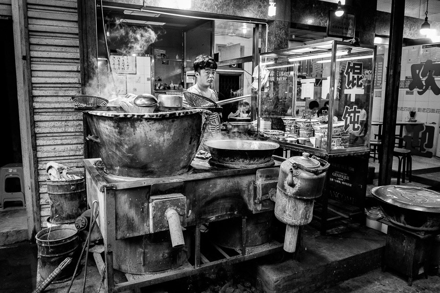 A man selling street food in the Muslim Quarter, Xi'an, China photographed with a wide-angle lens